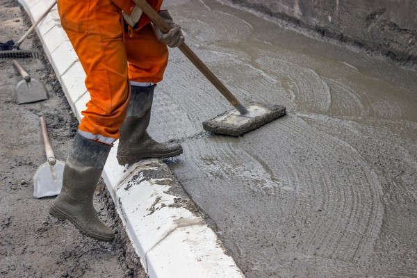 Workmen leveling fresh Concrete with concrete leveling tool, newly poured concrete sidewalk on a building site. An wooden bull float is being used to smooth a new sidewalk.